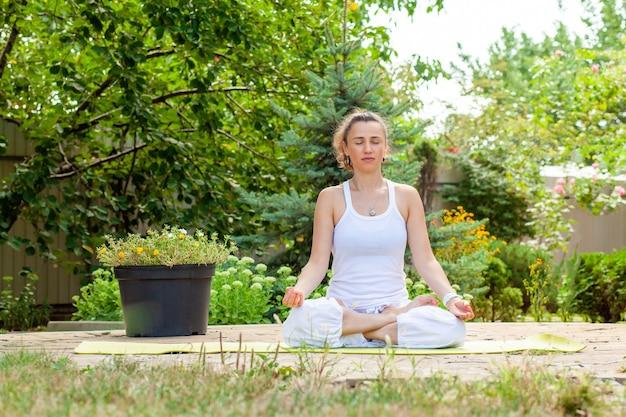 Mujer joven practica yoga en el jardín