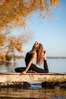 Mujer joven practicando ejercicio de yoga en el muelle tranquilo en el parque otoño