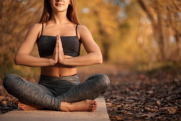 Mujer joven practicando ejercicio de yoga en el parque otoño con hojas amarillas. estilo de vida deportivo y recreativo