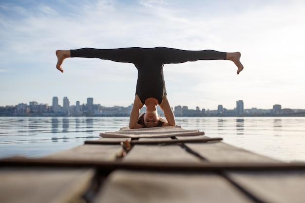 Mujer joven practicando ejercicio de yoga en el tranquilo muelle de madera con la ciudad. deporte y recreación en la ciudad