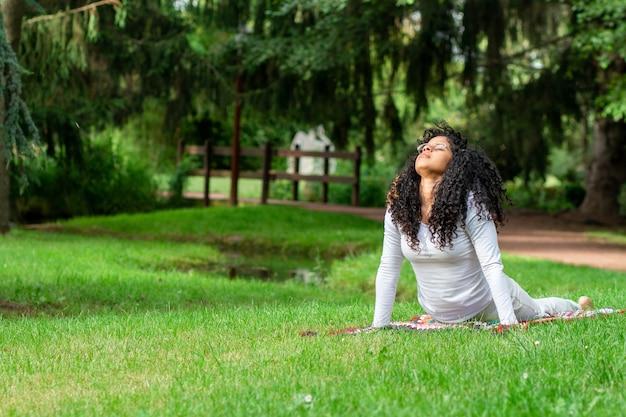 Mujer joven practicando posiciones de yoga en el parque rodeado de árboles