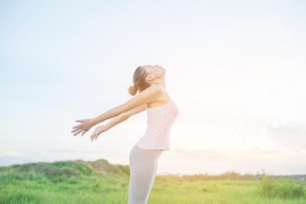 Mujer joven practicando posturas de yoga al aire libre
