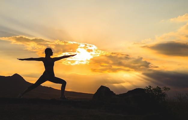 Mujer joven practicando yoga al atardecer en lugar de montaña hermosa.