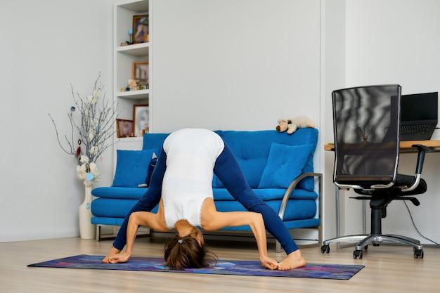 Mujer joven practicando yoga en casa, flexión hacia adelante y estiramiento