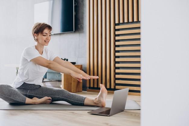 Mujer joven practicando yoga en casa en mat