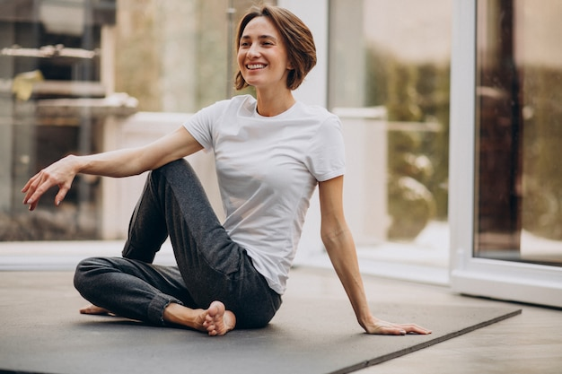 Mujer joven practicando yoga en casa