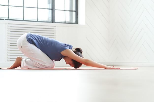 Mujer joven practicando yoga en una estera de yoga