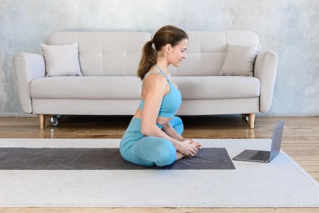 Mujer joven practicando yoga de estiramiento mientras ve la lección en video en la computadora portátil en casa