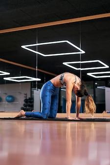 Mujer joven practicando yoga en un gimnasio, haciendo ejercicio en ropa deportiva azul, haciendo cat pose o marjaryasana.