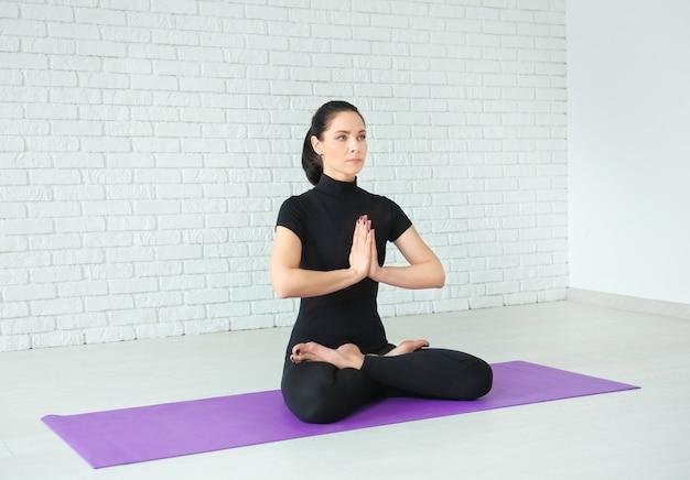 Mujer joven practicando yoga en el interior