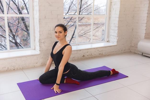 Mujer joven practicando yoga junto a la ventana