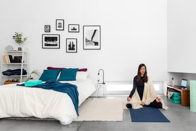 Mujer joven practicando yoga y meditación en posición de loto en dormitorio con interior de estilo minimalista