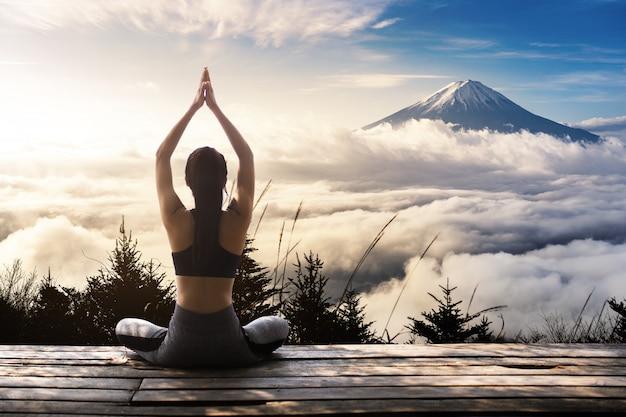 Mujer joven practicando yoga en la naturaleza