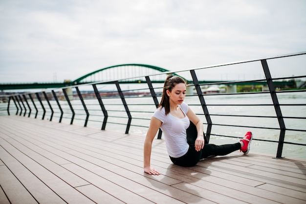 Mujer joven practicando yoga o estiramiento en el muelle de la ciudad.