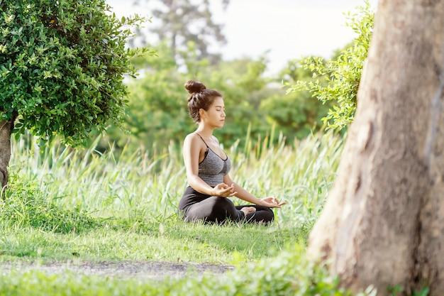 Mujer joven practicando yoga en el parque