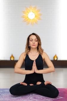 Mujer joven, practicar, yoga, meditación, en, gimnasio