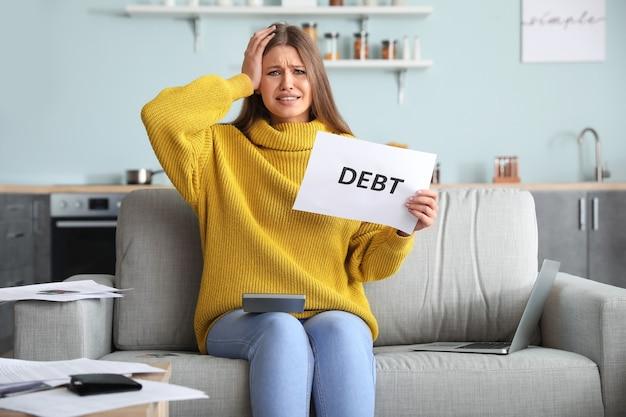 Mujer joven preocupada endeudada en casa