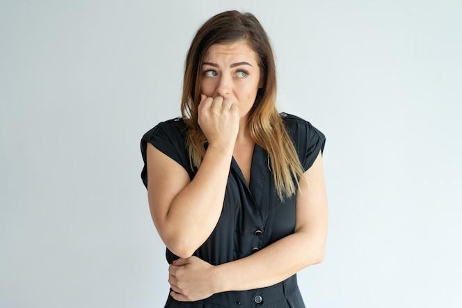 Mujer joven preocupada morderse las uñas mientras tiene ansiedad.