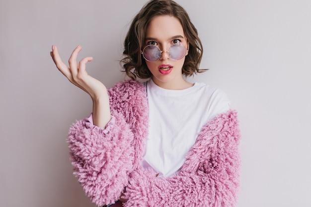Mujer joven preocupada con el pelo oscuro posando en la pared clara en abrigo de piel. filmación en interiores de hermosa niña caucásica en pie de chaqueta mullida.