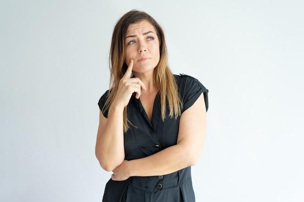 Mujer joven preocupada pensativa perdida en pensamientos y mirando lejos.