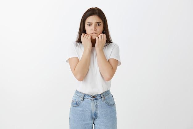 Mujer joven preocupada posando contra la pared blanca