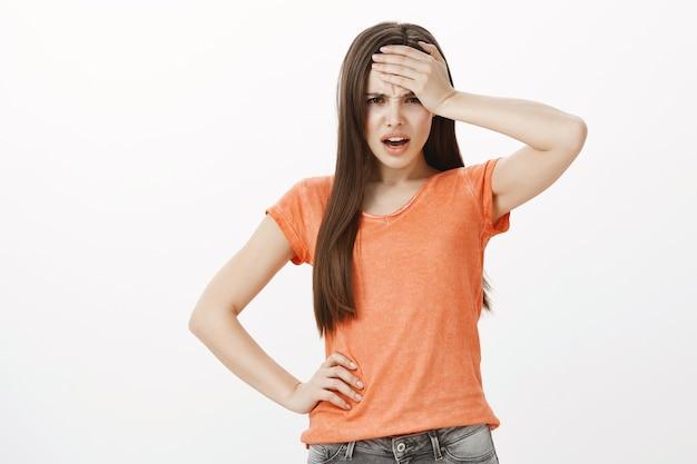 Mujer joven preocupada y preocupada se golpea la frente y se ve frustrada o ansiosa