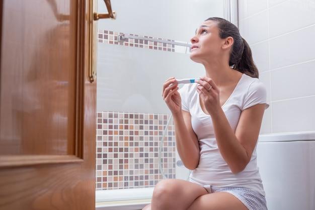 Mujer joven, preocupada por los resultados de la prueba de embarazo en casa