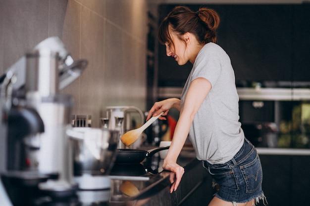 Mujer joven preparando el desayuno en la cocina por la mañana