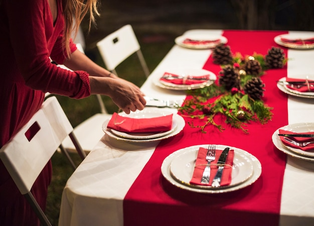 Mujer joven preparando la mesa para la cena de navidad