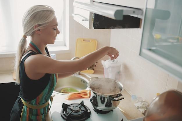Mujer joven preparando sopa de calabaza