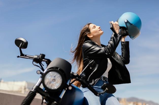 Mujer joven preparándose para andar en motocicleta en la ciudad