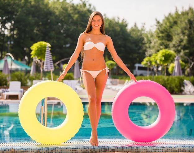 La mujer joven está presentando con los anillos de goma coloreados en piscina.