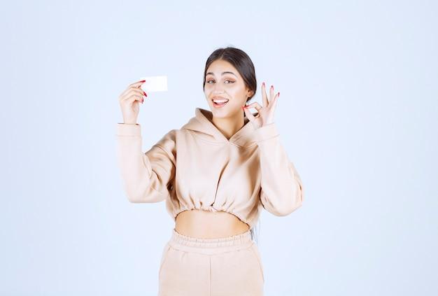Mujer joven presentando su tarjeta de visita y mostrando buena señal