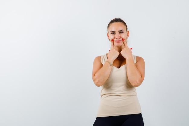 Mujer joven presionando los dedos en las mejillas en camiseta sin mangas beige y luciendo lindo