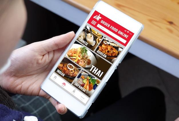Mujer joven de primer plano con teléfono inteligente con aplicación en línea de comida de pedido
