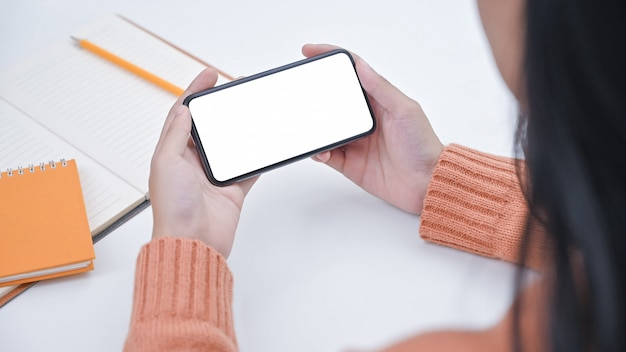 Mujer joven del primer que sostiene smartphone con la pantalla aislada.