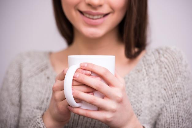 La mujer joven del primer está sosteniendo una taza de té.