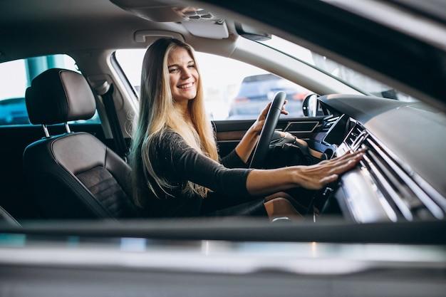Mujer joven probando un automóvil desde una sala de exposición de automóviles