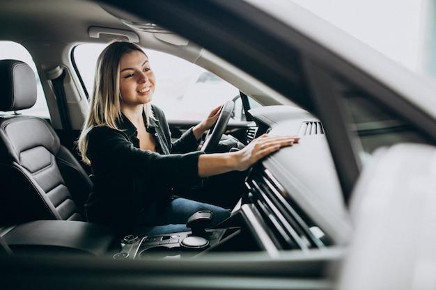 Mujer joven probando un automóvil en una sala de exposición de automóviles