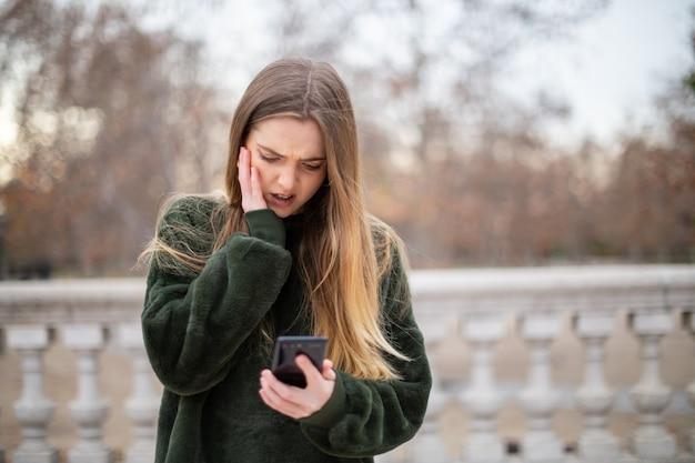 Mujer joven con problemas frotando la frente y mirando el teléfono inteligente moderno mientras está de pie en el parque otoño