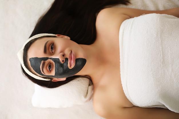 Mujer joven con procedimiento de máscara en el centro de spa