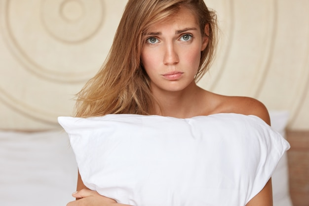 Una mujer joven profundamente alterada se sienta en la cama de su casa, se siente sola y triste, sufre de insomnio, abraza la almohada o tiene algún desacuerdo con su novio después de pasar la noche juntos. concepto de insomnio