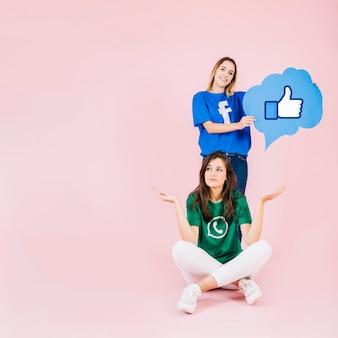 Mujer joven con los pulgares encima de la burbuja del discurso de la muestra detrás de su amigo encogiéndose de hombros