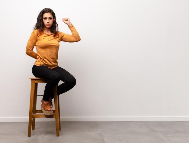 Mujer joven con el puño en alto, sentado en una silla junto a copyspace