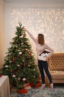 Mujer joven de puntillas decorando el árbol de navidad, sosteniendo algunos adornos navideños en su mano
