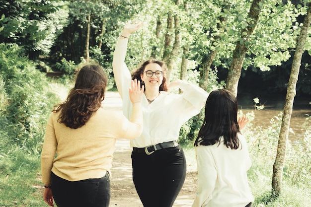 Una mujer joven a punto de chocar los cinco con dos amigos, la amistad y el concepto de diversión, día de bosque, soleado