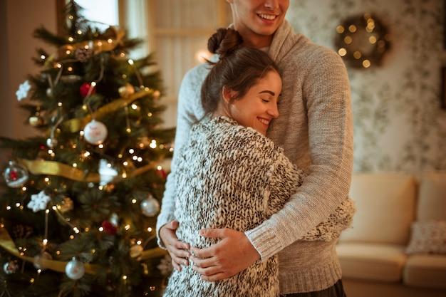 Mujer joven que abraza al hombre cerca de abeto decorado
