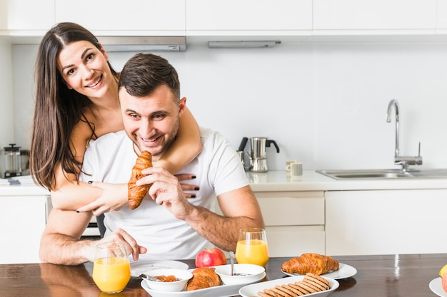 Mujer joven que abraza a su novio que desayuna en la cocina