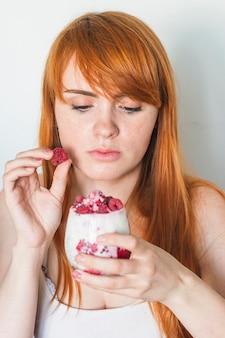 Mujer joven que agrega la frambuesa en vidrio del yogur