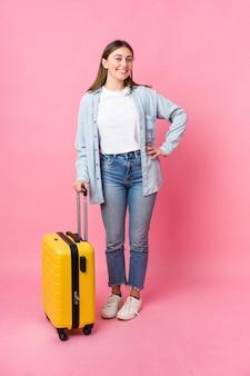 Mujer joven que va al viajero aislado en la pared rosa